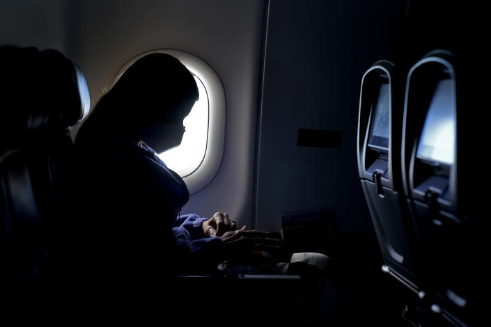 A passenger wears a face mask she travels on a Delta Airlines flight Wednesday, Feb. 3, 2021, after taking off from Hartsfield-Jackson International Airport in Atlanta. Amid fears of new variants of the virus, new restrictions on movement have hit just as people start to look ahead to what is usually a busy time of year for travel. (AP Photo/Charlie Riedel)