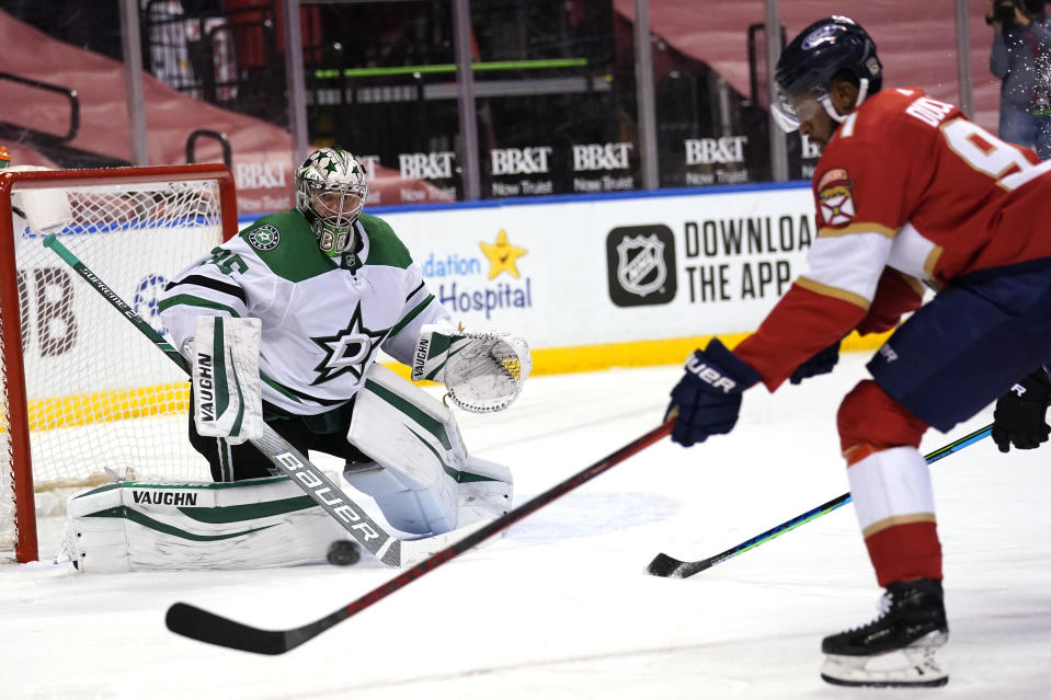 Dallas Stars goaltender Anton Khudobin, left, defends a shot on the goal by Florida Panthers left wing Anthony Duclair (91) during the second period of an NHL hockey game, Monday, Feb. 22, 2021, in Sunrise, Fla. (AP Photo/Lynne Sladky)