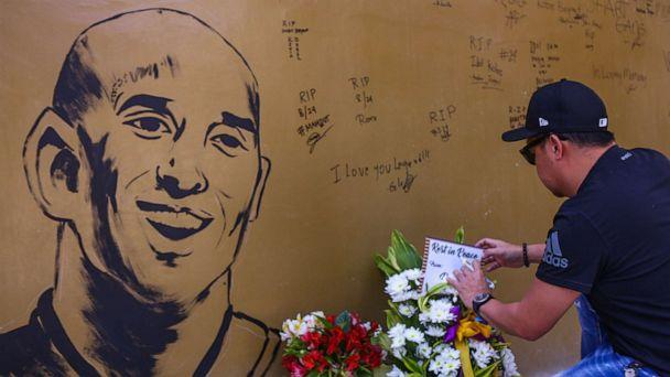 PHOTO: A fan places flowers to mourn former Los Angeles Lakers basketball player Kobe Bryant following his death overnight in the US, near the 'House of Kobe' gym built in honour of his 2016 visit to the Philippines, in Manila on January 27, 2020. (Maria Tan/AFP via Getty Images)