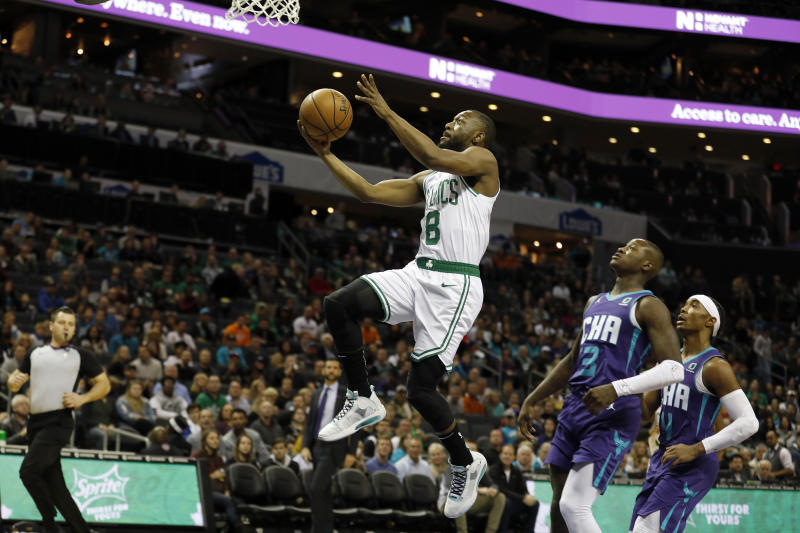 Boston Celtics' Kemba Walker (8) slips by for an easy two as Charlotte Hornets' Terry Rozier (3) and Devonte' Graham (4) trail in the paint during the first half of an NBA basketball game in Charlotte, N.C., Tuesday, Dec. 31, 2019. (AP Photo/Bob Leverone)