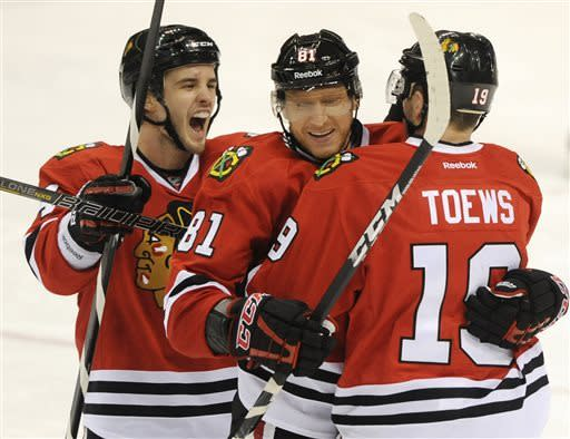 Chicago Blackhawks' Marian Hossa (81), of Slovakia, celebrates his goal against the St. Louis Blues with Jonathan Toews,(19) and Niklas Hjalmarsson, left, of Sweden, in the third period of an NHL hockey game on Sunday, April 14, 2013, in St. Louis. Chicago won 2-0. (AP Photo/Bill Boyce)