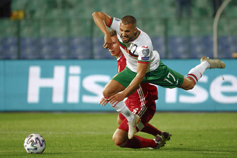 Bulgaria's Georgi Yomov, right, falls after a tackle by Hungary's Willi Orban during the Euro 2020 playoff semifinal soccer match between Bulgaria and Hungary at the Vasil Levski stadium in Sofia, Bulgaria, on Thursday Oct. 8, 2020. (AP Photo/Desislava Komarova)