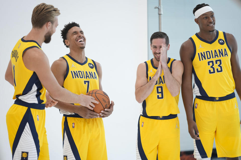 Indiana Pacers forward Domantas Sabonis, left, laughs with team mates Malcolm Brogdon (7), T.J. McConnell (9) and Myles Turner (33) while waiting for a photo shoot during the NBA basketball team's media day in Indianapolis, Monday, Sept. 27, 2021.(AP Photo/AJ Mast)