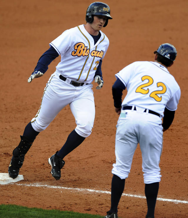 Montgomery Biscuit's Jeff Malm (23) is greeted by manager Brady Williams (22) as he rounds third after hitting a 2-run home run against the Tampa Bay Rays in a spring exhibition baseball game in Montgomery, Ala., Saturday, March 29, 2014. (AP Photo/Montgomery Advertiser, Mickey Welsh)