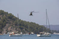 A helicopter takes water to pour on a wildfire that burns the forest in Turgut village, near tourist resort of Marmaris, Mugla, Turkey, Wednesday, Aug. 4, 2021. As Turkish fire crews pressed ahead Tuesday with their weeklong battle against blazes tearing through forests and villages on the country's southern coast, President Recep Tayyip Erdogan's government faced increased criticism over its apparent poor response and inadequate preparedness for large-scale wildfires.(AP Photo/Emre Tazegul)