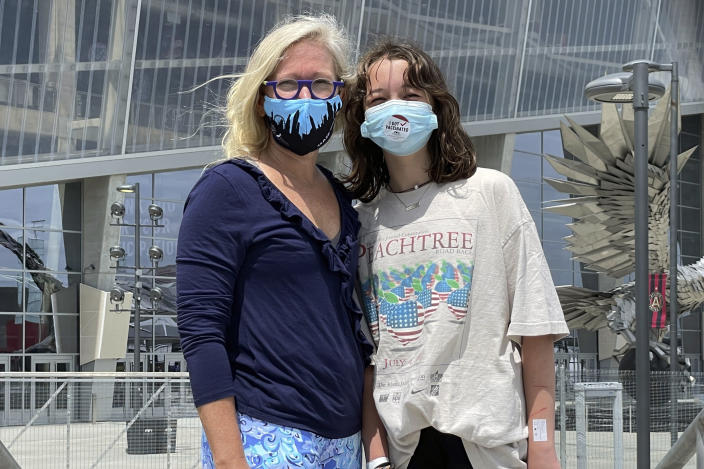 English Norman and her 12-year-old daughter, Jane Ellen Norman, pose for a photo outside Mercedes-Benz Stadium in Atlanta on Tuesday, May 11, 2021. Jane Ellen and her 14-year-old brother Owen were vaccinated Tuesday morning, just after U.S. regulators expanded use of Pfizer's COVID-19 shot to those as young as 12. (AP Photo/Angie Wang)
