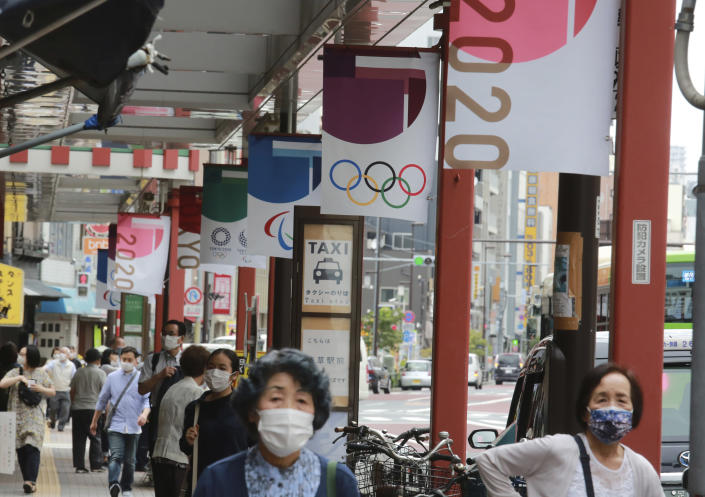 People wearing face masks to help protect against the spread of the coronavirus walk under the banner of Tokyo Olympics along a walkway in Tokyo, Wednesday, June 30, 2021. (AP Photo/Koji Sasahara)