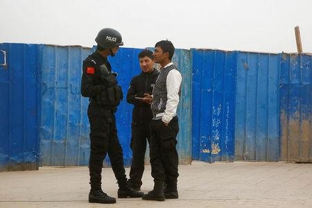 A police officer talks to men in a street in Kashgar, Xinjiang Uighur Autonomous Region, China, March 24, 2017.  REUTERS/Thomas Peter