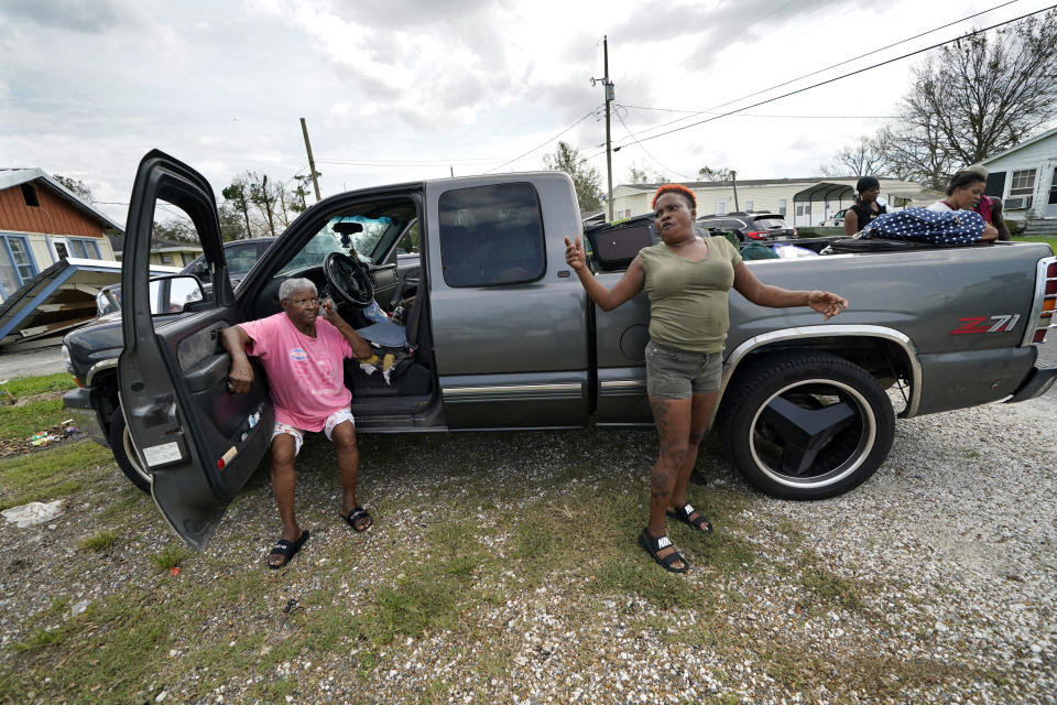 Loubertha Rideaux, left, sits on the door jamb of a truck in Lake Charles, La., as her daughter Patricia Mingo Lavergne reacts, after they returned form evacuation in the aftermath of Hurricane Laura, Sunday, Aug. 30, 2020. They evacuated and returned in the truck with eight adults and one child. (AP Photo/Gerald Herbert)