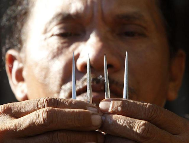 Ruben Enaje, 52, who will portray as Jesus Christ for the 27th time, shows three-inch nail which he will use on a Good Friday crucifixion re-enactment in San Pedro Cutud town, Pampanga province, north of Manila. The Roman Catholic church frowns on the gory spectacle held in the Philippine village of Cutud every Good Friday but that does nothing to deter the faithful from emulating the suffering of Christ and taking a painful route to penitence.