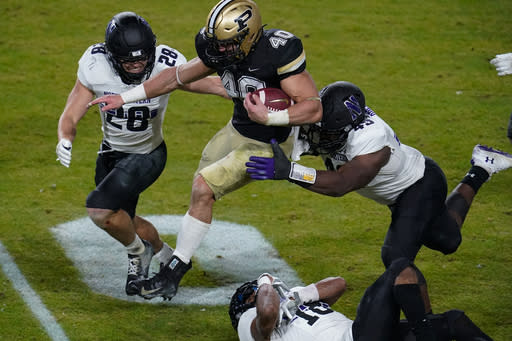 Purdue running back Zander Horvath (40) leaps between Northwestern linebacker Chris Bergin (28) and defensive lineman Adetomiwa Adebawore (49) during the third quarter of an NCAA college football game in West Lafayette, Ind., Saturday, Nov. 14, 2020. (AP Photo/Michael Conroy)