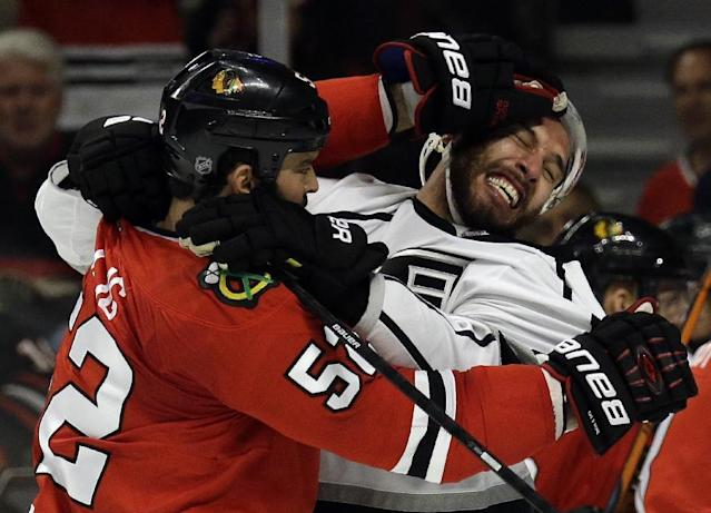 Chicago Blackhawks left wing Brandon Bollig (52) and Los Angeles Kings left wing Dwight King (74) fight during the first period in Game 7 of the Western Conference finals in the NHL hockey Stanley Cup playoffs Sunday, June 1, 2014, in Chicago. (AP Photo/Nam Y. Huh)