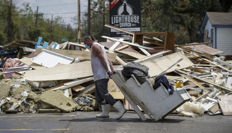 Joey Vene, a member of New Beginnings in Harvey, La., drags the baptismal stairs to the debris pile while helping gut the Lighthouse Church in Lafitte, La., Tuesday, Sept. 7, 2021, in the aftermath of Hurricane Ida. (David Grunfeld/The Times-Picayune/The New Orleans Advocate via AP)