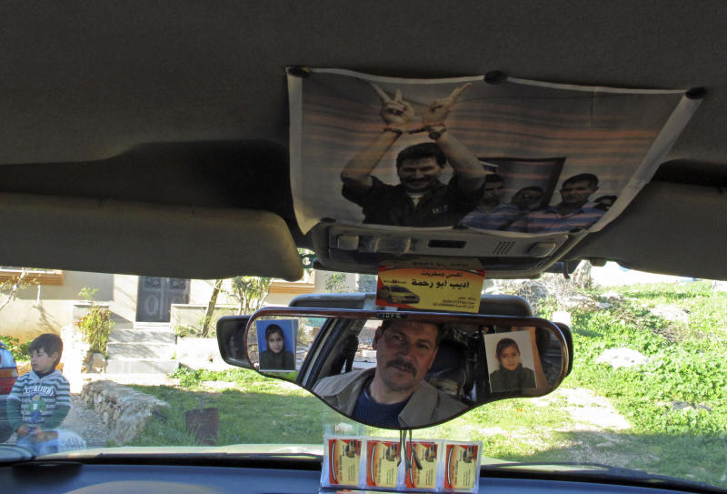 """In this Feb. 3, 2013 photo, Palestinian Adib Abu Rahmeh, activist and resident of the West Bank village of Bilin, sits in his taxi where he has pasted a photograph of himself during a court hearing in an Israeli military prison. Dozens of Bilin men and youths were detained and arrested over the past eight years, accused of throwing stones or organizing protests against Israel's separation barrier that has swallowed much of the village's farmland. An Oscar-nominated documentary """"Five Broken Cameras"""" is the story of a yearslong struggle by residents of Bilin to wrest their village lands back from Israel's military. (AP Photo/Diaa Hadid)"""