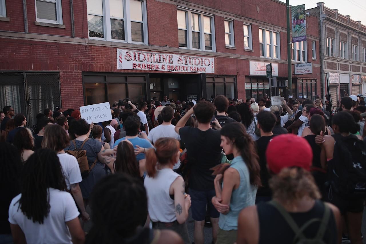 <p>Demonstrators rally outside the Sideline Studio Barber & Beauty Salon in the South Shore neighborhood protesting the shooting death of 37-year-old Harith Augustus who worked there as a barber on July 16, 2018 in Chicago, Ill. (Photo: Scott Olson/Getty Images) </p>