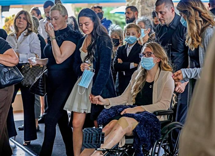 Tayler Scheinhaus and Deven Gonzalez hold hands as they arrive for the funeral of their stepfather and father, Edgar Gonzalez, at Christ Fellowship Church in Palmetto Bay on Friday, July 23, 2021. Edgar, a Miami attorney who graduated from Christopher Columbus High, died during the June 24, 2021, collapse of the 12-story oceanfront condo, Champlain Towers South in Surfside.