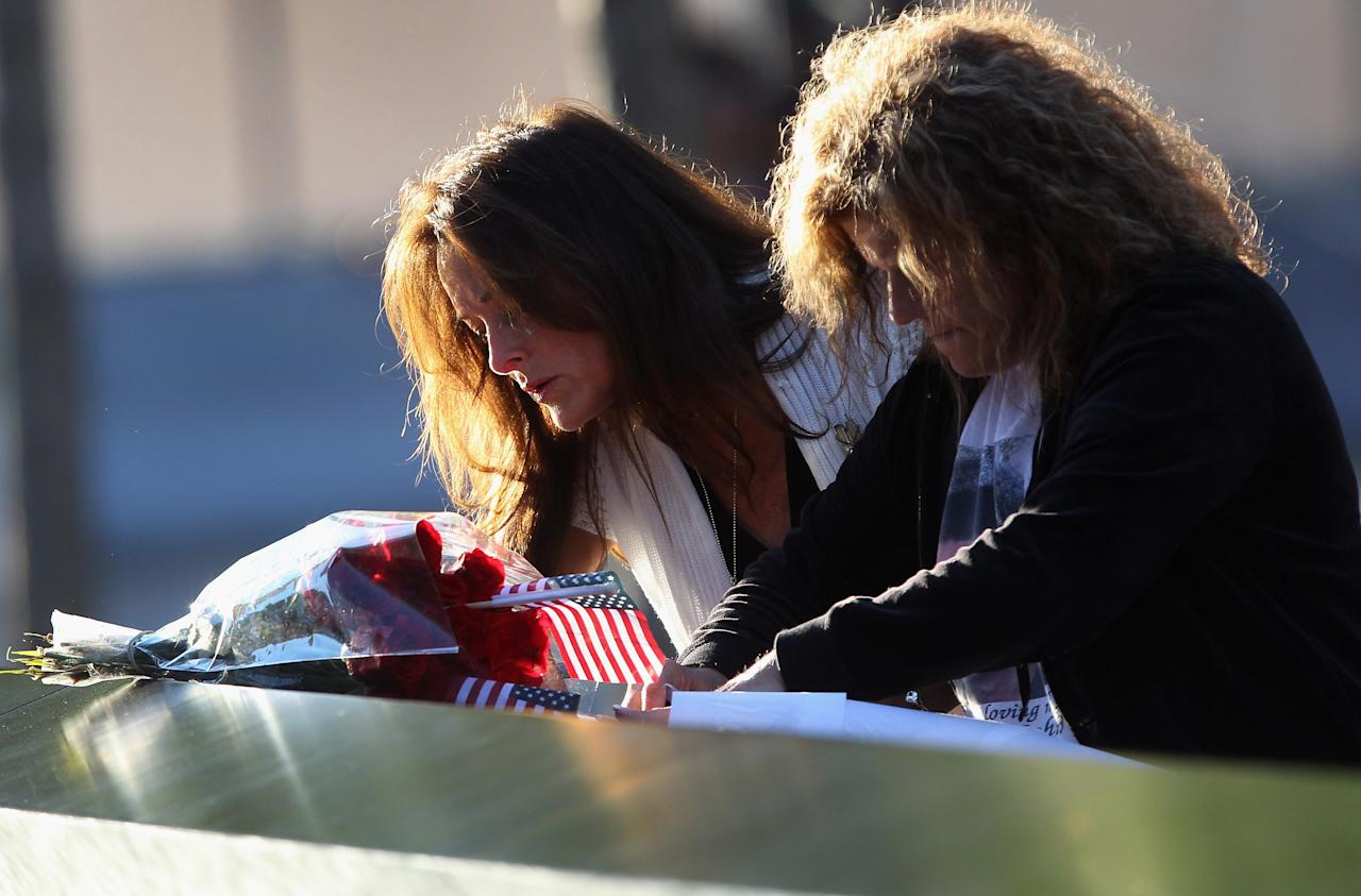 Tina Grazioso, left, looks at the name of her husband, John Grazioso, at the World Trade Center Memorial, who died in the attacks at the World Trade Center, during the 11th anniversary observance, in New York, Tuesday Sep. 11, 2012. At right is John Grazioso's sister Carolee Azzarello. (AP Photo/John Moore, Getty Images, Pool)