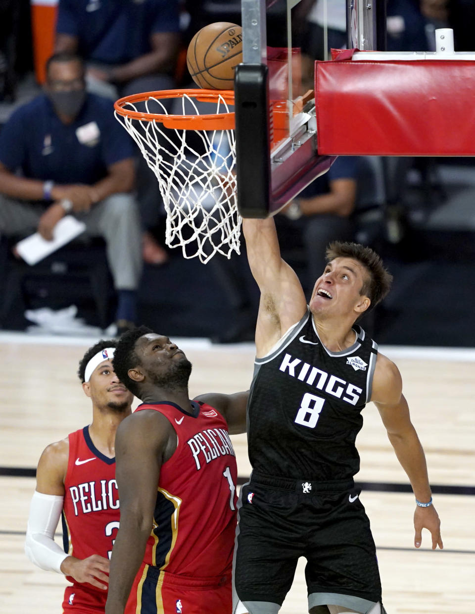 Sacramento Kings' Bogdan Bogdanovic (8) goes up for a basket against New Orleans Pelicans' Zion Williamson (1) and Josh Hart (3) during the second half of an NBA basketball game Thursday, Aug. 6, 2020 in Lake Buena Vista, Fla. (AP Photo/Ashley Landis, Pool)