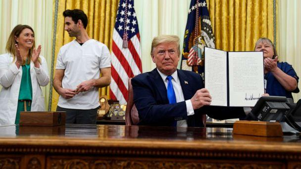 PHOTO: President Donald Trump holds a signed proclamation in honor of World Nurses Day during an event in the Oval Office of the White House, May 6, 2020, in Washington. (Evan Vucci/AP)