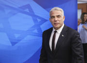 """Israeli Alternate Prime Minister and Foreign Minister Yair Lapid arrives for the first weekly cabinet meeting of the new government in Jerusalem, Sunday, June 20, 2021. Prime Minister Naftali Bennett opened his first Cabinet meeting on Sunday since swearing in his new coalition government with a condemnation of the newly elected Iranian president, whom he called """"the hangman of Tehran."""" (Emmanuel Dunand/Pool Photo via AP)"""