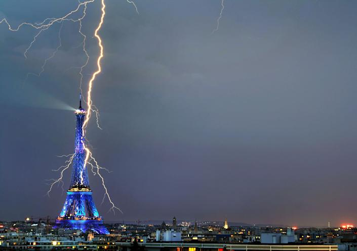 """""""I quickly grabbed my camera and put it on a tripod by the window,"""" said the 31-year-old photographer who caught the moment the Eiffel Tower appeared to be struck by lightning. The photo, taken from his apartment window last year, surfaced this week and won the Office du Tourisme de Paris competition. It will be part of an upcoming show in France. (Photo: Caters News)"""