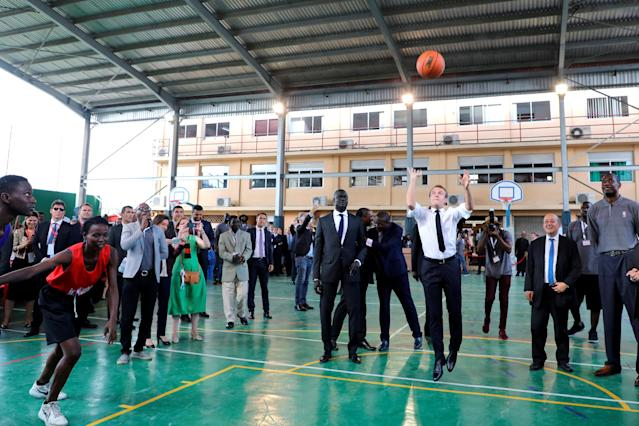 French President Emmanuel Macron throws the ball during a meeting with former pro basketball players from NBA Africa and takes part in a practice session with young basketball players in the French Louis Pasteur high school in Lagos, Nigeria, July 4, 2018. Ludovic Marin/Pool via Reuters