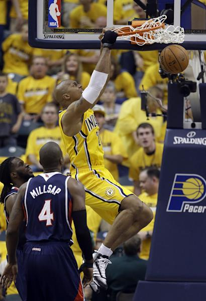 Indiana Pacers' David West (21) dunks against Atlanta Hawks' Paul Millsap (4) during the first half in Game 1 of an opening-round NBA basketball playoff series on Saturday, April 19, 2014, in Indianapolis. (AP Photo/Darron Cummings)