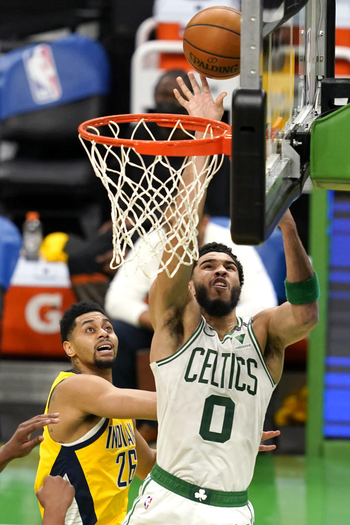 Boston Celtics forward Jayson Tatum (0) drives to the hoop past Indiana Pacers guard Jeremy Lamb (26) in the second half of an NBA basketball game, Friday, Feb. 26, 2021, in Boston. (AP Photo/Elise Amendola)
