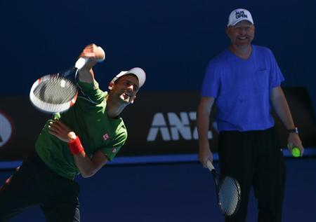 Djokovic serves as his coach Becker watches during a practice session at the Australian Open 2014 tennis tournament in Melbourne