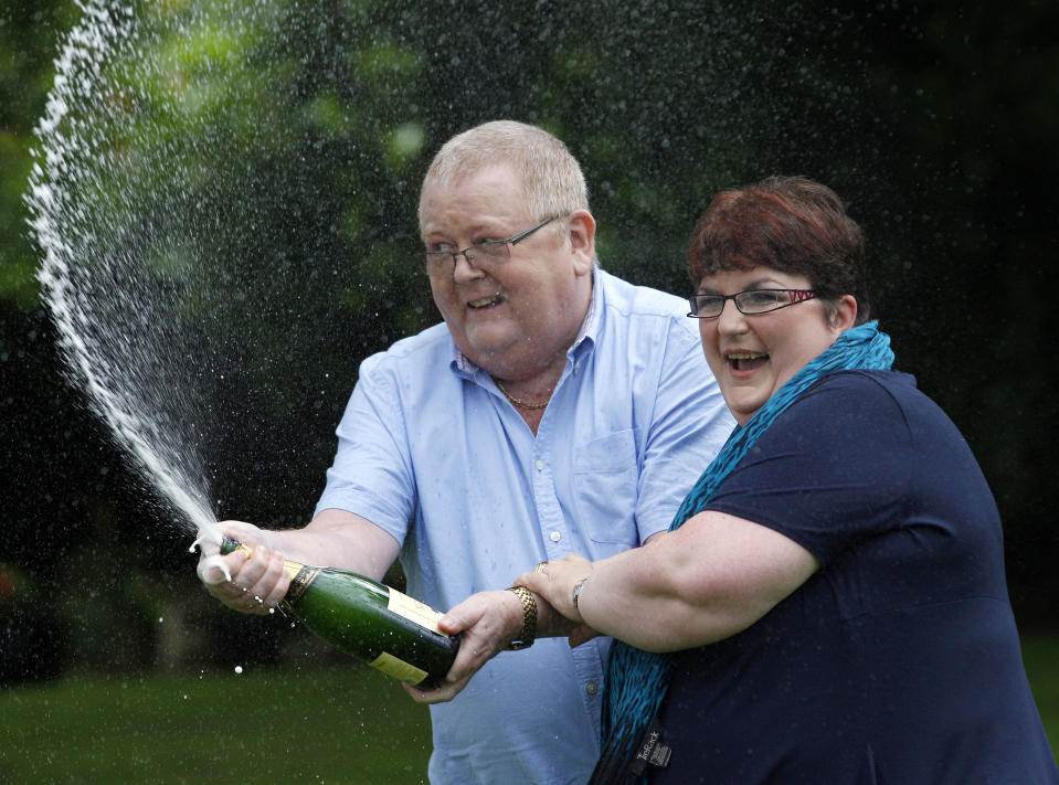 Colin Weir (L) and his wife Chris spray a bottle of champagne after a news conference at a hotel near Falkirk, Scotland July 15, 2011. The couple scooped 161 million pounds ($259 million) in Tuesday's Euromillions jackpot.   REUTERS/David Moir (BRITAIN - Tags: SOCIETY)