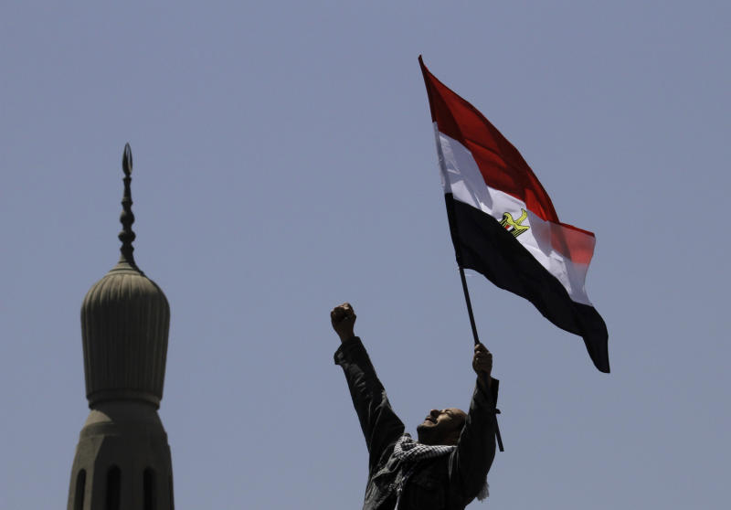 An Egyptian protester chants slogans and waves a national flag in front of a minaret at Tahrir Square, the focal point of Egyptian uprising, in Cairo, Egypt, Friday, April 20, 2012. Tens of thousands of protesters packed Cairo's downtown Tahrir Square on Friday in the biggest demonstration in months against the ruling military, aimed at stepping up pressure on the generals to hand over power to civilians and bar ex-regime members from running in upcoming presidential elections. (AP Photo/Amr Nabil)