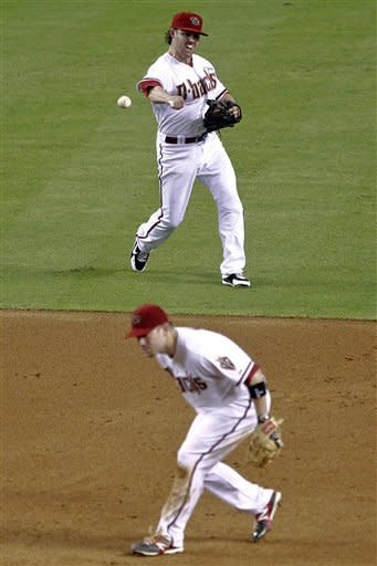 Arizona Diamondbacks' Jake Elmore unsucessfully tries to throw out Miami Marlins' Gorkys Hernandez as Diamondbacks' Aaron Hill ducks on the play during the sixth inning of a baseball game, Tuesday, Aug. 21, 2012, in Phoenix. (AP Photo/Matt York)