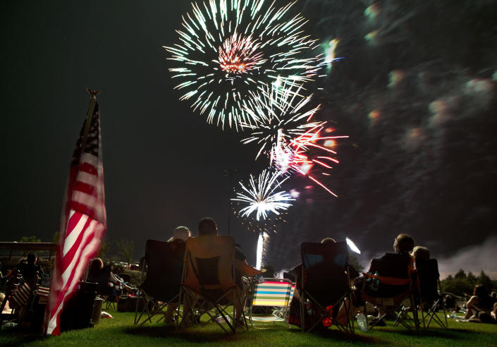 FILE - In this July 4, 2013, file photo, people watch as fireworks explode overhead during the Fourth of July celebration at Pioneer Park in Prescott, Ariz. For many Americans, the Fourth of July won't be about big festivities but setting off fireworks themselves. Hundreds of cities have canceled shows Saturday because of the coronavirus pandemic, and sales of consumer fireworks are booming. (AP Photo/Julie Jacobson, File)