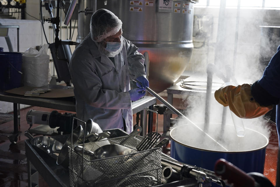 Rabbi Joseph Schwartz helps with the koshering of the production line and instruments used for Hanan Products' kosher-for-passover production run, Thursday, Jan. 7, 2021, in Hicksville, N.Y. (AP Photo/Seth Wenig)
