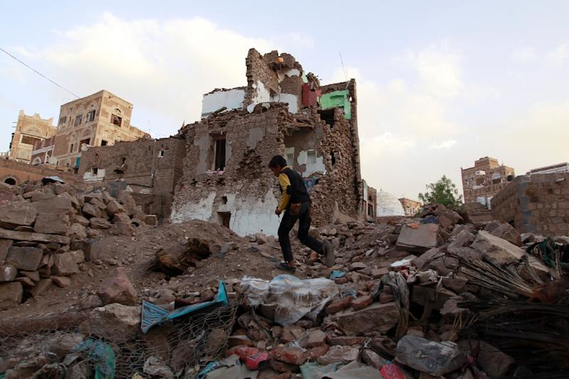 A Yemeni boy running past buildings that were damaged by air strikes carried out by the Saudi-led coalition in the capital Sanaa on March 23, 2016