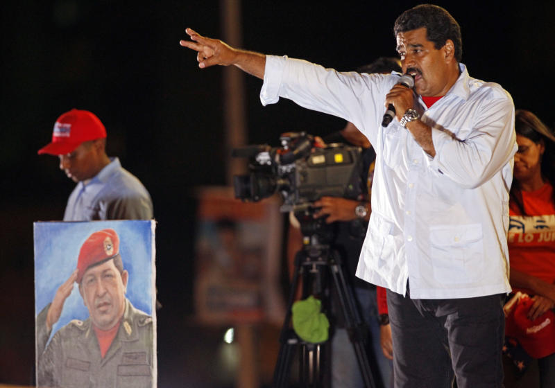 Venezuela's acting President Nicolas Maduro speaks during his closing campaign rally in Caracas, Venezuela, Thursday, April 11, 2013. Maduro, the hand-picked successor of Venezuela's late President Hugo Chavez whose portrait stands at left, is running for president against opposition candidate Henrique Capriles on April 14.  (AP Photo/Ramon Espinosa)