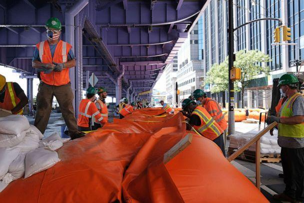 PHOTO: Workers erect temporary flood barriers in the South Street Seaport neighborhood in preparation for potential flooding and a storm surge from Tropical Storm Isaias, Aug. 3, 2020, in New York. (Spencer Platt/Getty Images)
