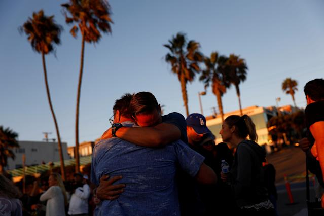 <p>People embrace during a memorial for Rachael Parker and Sandy Casey, victims of the October 1st Las Vegas Route 91 music festival mass shooting, in Manhattan Beach, Calif., Oct. 4, 2017. (Photo: Patrick T. Fallon/Reuters) </p>