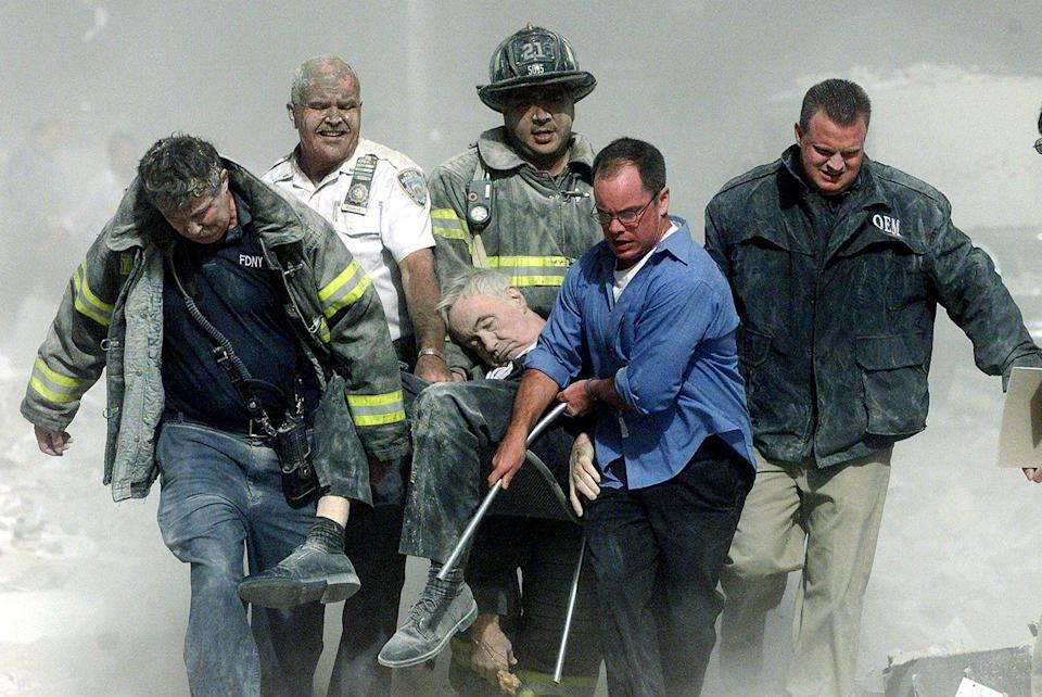 <p>Rescue workers carry fatally injured New York City Fire Department chaplain, the Rev. Mychal Judge, from the wreckage of the World Trade Center.</p>
