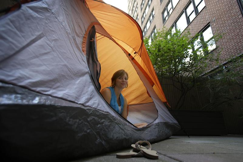"Kathleen Boyle poses for a picture in a tent on the patio of her room at the Affina Hotel in New York, Thursday, Aug. 15, 2013. A couple of New York City locales are offering an unusual option _ the chance to sleep outdoors, incredibly comfortably. It's an urban take on ""glamping,"" where hotel comforts are taken outside. (AP Photo/Seth Wenig)"