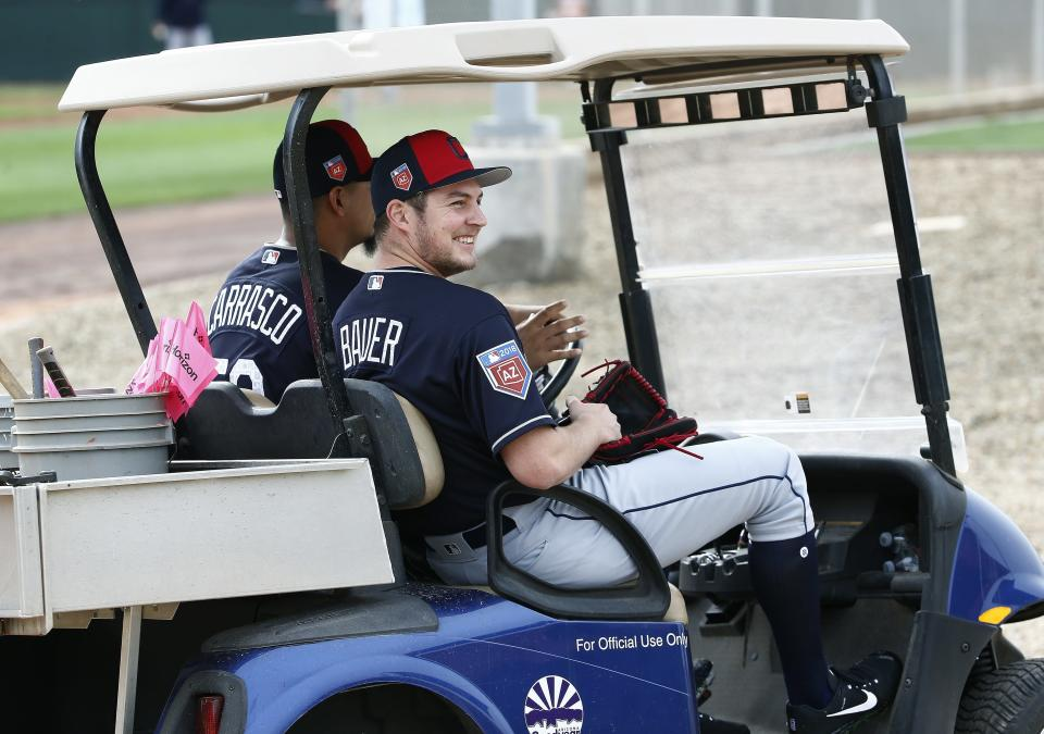 Trevor Bauer and Carlos Carrasco cruise in a golf cart during spring training. (AP)
