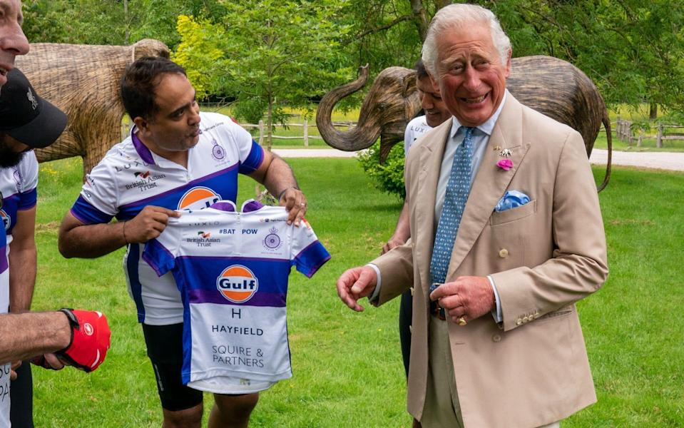 Prince Charles receives a cycling jersey from event organiser Rohit Chadda - Arthur Edwards - WPA Pool/Getty Images