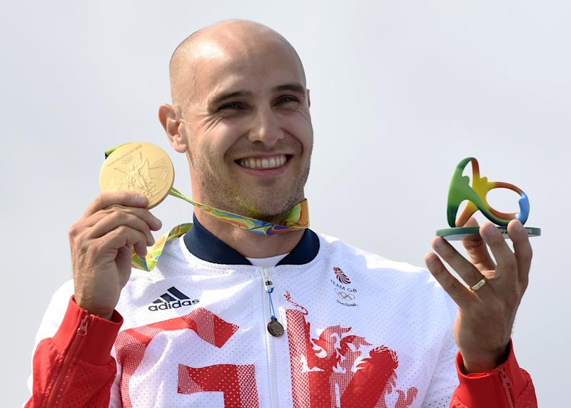Britain's Liam Heath celebrates on the podium after winning the K1 200m title at the 2016 Rio Olympics