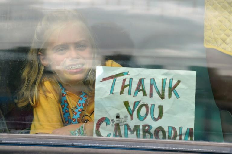 A young passenger from the Westerdam cruise ship holds up a sign on a bus after disembarking in Sihanoukville