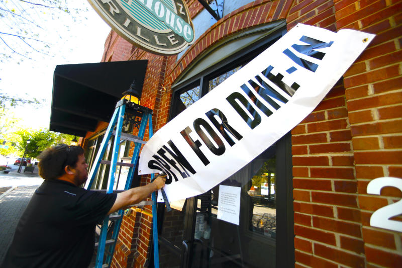 Jason Godbey hangs a banner over the entrance of Madison Chop House Grille as they prepare to shift from take out only to dine-in service Monday, April 27, 2020, in Madison, Ga. Gov. Brian Kemp eased restrictions on restaurants as long as guide lines are followed to prevent to spread of the Coronavirus. (AP Photo/John Bazemore)
