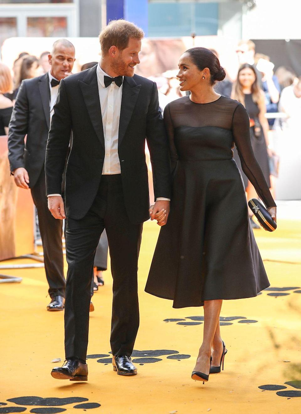 <p>Wearing matching black tie attire for the 'The Lion King' European premiere in London on 14 July, the Duke and Duchess of Sussex looked smitten as they walked the yellow-coloured carpet before meeting Beyoncé and Jay-Z. </p>