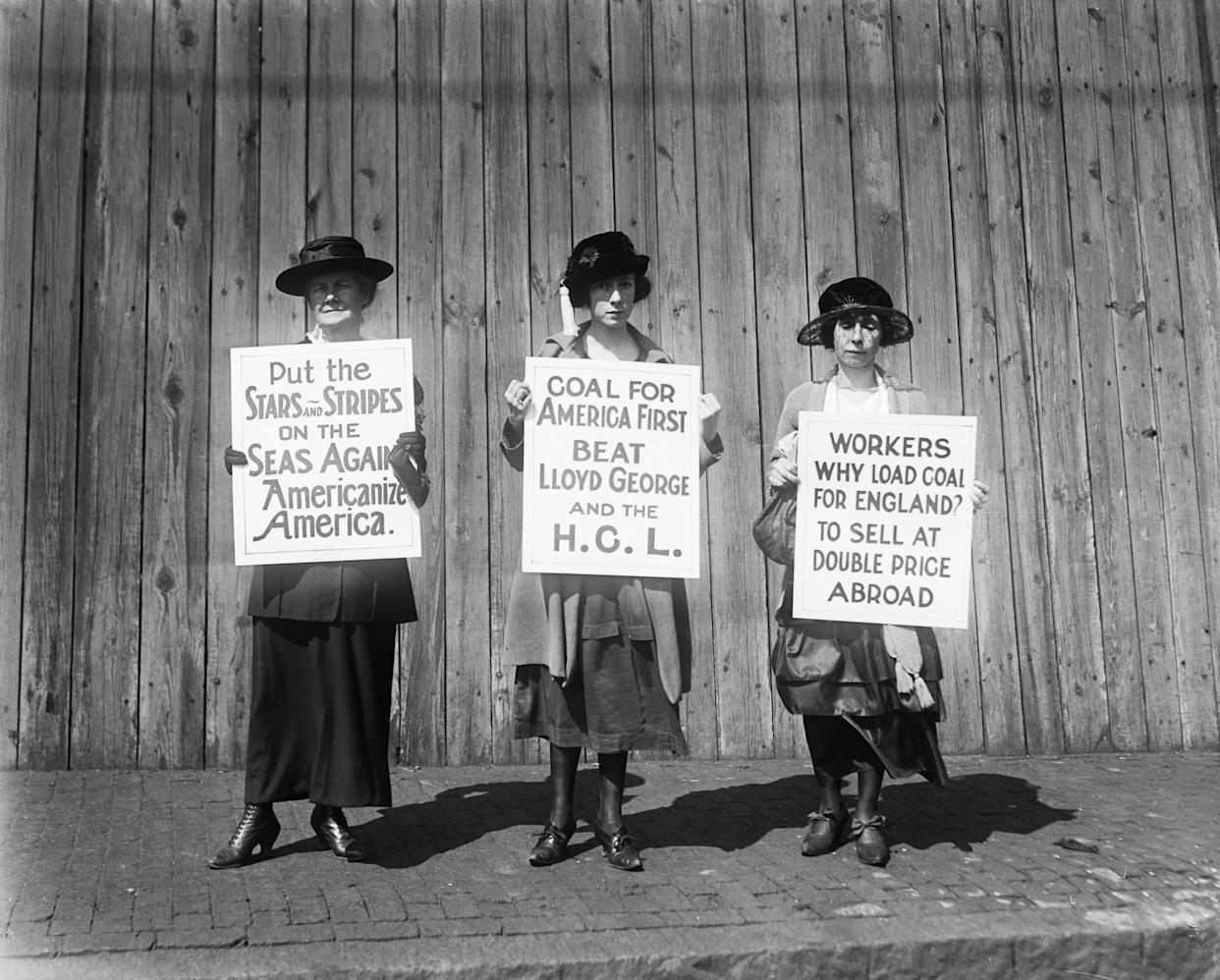 Boston women pickets are centering their drive to prevent the export of coal to that England on Sep. 22, 1920. Three of the women pickets are shown patrolling the waterfront in East Boston. The picketing is designed, the leaders said, to thwart the effort of Lloyd George to import 150,000,000 tons of coal from America to England thus breaking the strike of British Coal Miners.