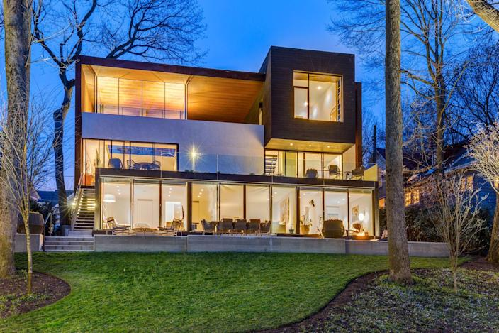 Designed by architect David Jameson, this Bethesda home includes areas for indoor-outdoor living on each level including the office's covered deck with views of the Potomac. The lower level houses three bedrooms, a lounge, a family room, and a wine cellar. A pool, a hot tub, and a pool house are located down a hill from the home.