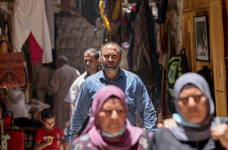 Palestinian human rights activist Issa Amro walks through the market of Hebron's old city in the occupied West Bank, on June 27