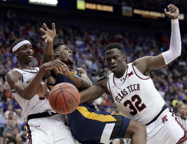 West Virginia's Derek Culver, center, battles Texas Tech's Tariq Owens, left, and Norense Odiase (32) for a loose ball during the second half of an NCAA college basketball game in the Big 12 men's tournament Thursday, March 14, 2019, in Kansas City, Mo. West Virginia won 79-74. (AP Photo/Charlie Riedel)